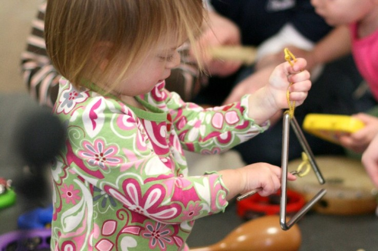Child experimenting with a triangle during a Music Together Class